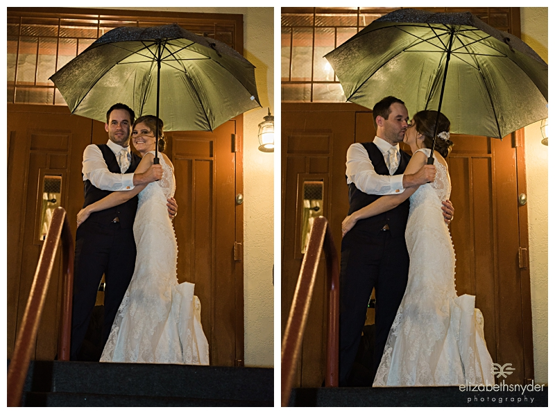 Bride and groom share a moment in the rain at the end of the night