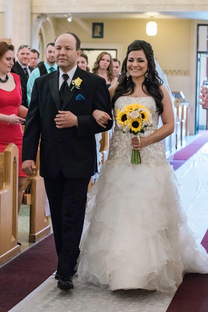 A bride and her father walk down the aisle