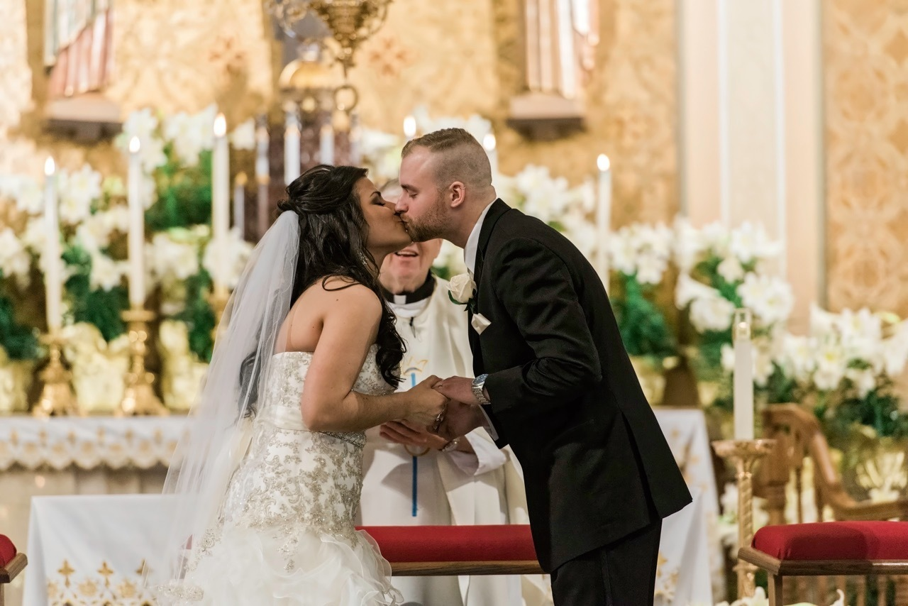A first kiss between a bride and groom