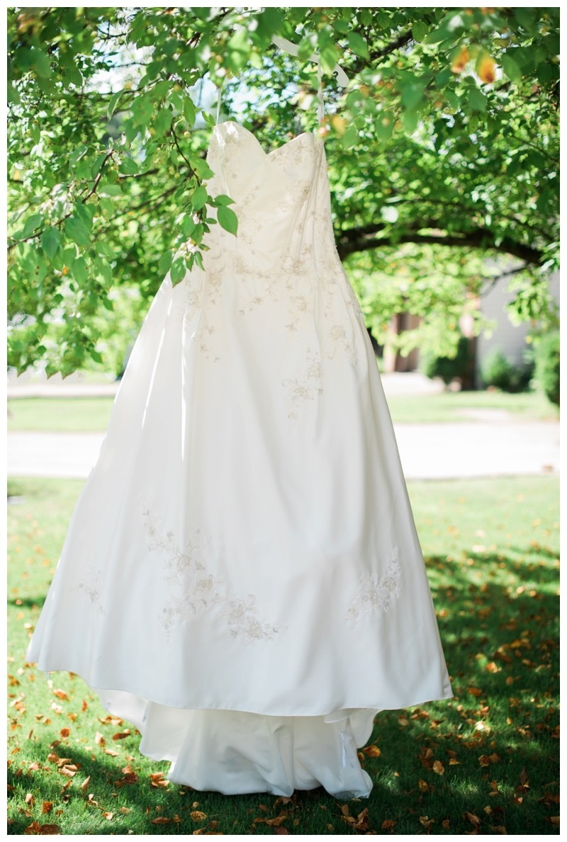 A brides dress hangs in front of her mother's house.