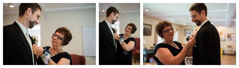 A groom has his boutonniere pinned on by his mother.